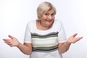 Having no clue. Cropped image of elderly woman shrugging her shoulders with clueless expression while standing against white background